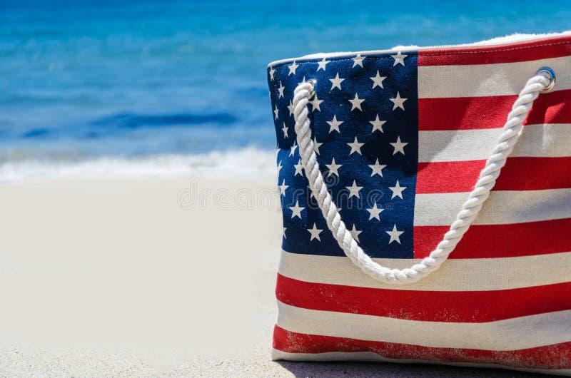 De zak met Amerikaanse vlag kleurt dichtbij oceaan op het zandige strand stock foto