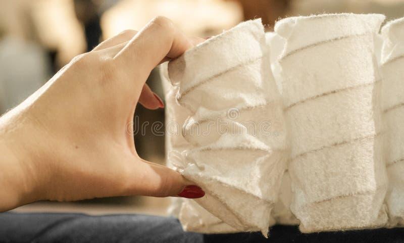 De zak onafhankelijke lente bij de internationale tentoonstelling van professioneel meubilair Matrasmateriaal in de handen van ee stock afbeeldingen
