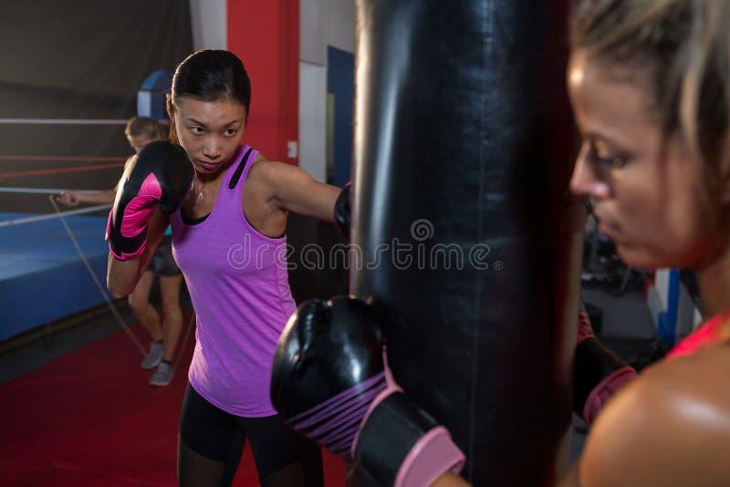 De zak van de atletenholding terwijl zeker vrouwelijk bokserponsen stock foto's
