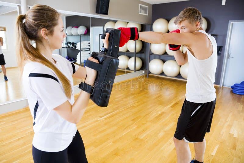 De Zak van het bokserponsen door Vrouwelijke Instructeur wordt gehouden die stock afbeeldingen