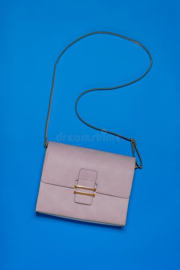 De zak van lichte leervrouwen op blauwe achtergrond Het leertoebehoren van moderne vrouwen Vlak leg royalty-vrije stock afbeelding