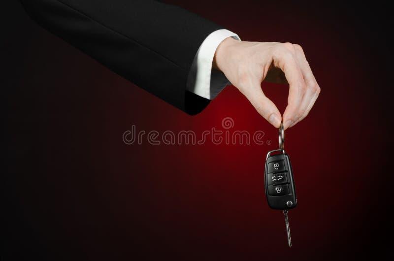 De zaken en de gift als thema hebben: de autoverkoper in een zwart kostuum houdt de sleutels aan een nieuwe auto op een donkerrod royalty-vrije stock afbeeldingen