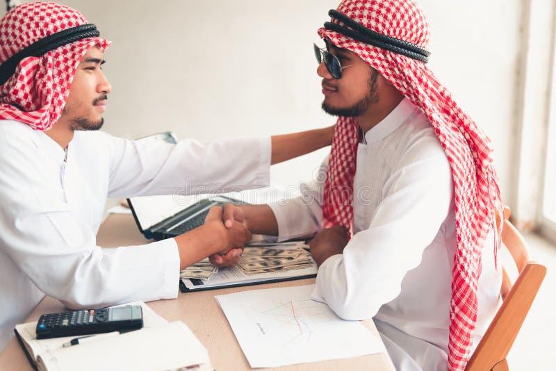 De zakenlieden Arabier zijn de overeenkomst van het handtekeningscontract en handsha stock foto's