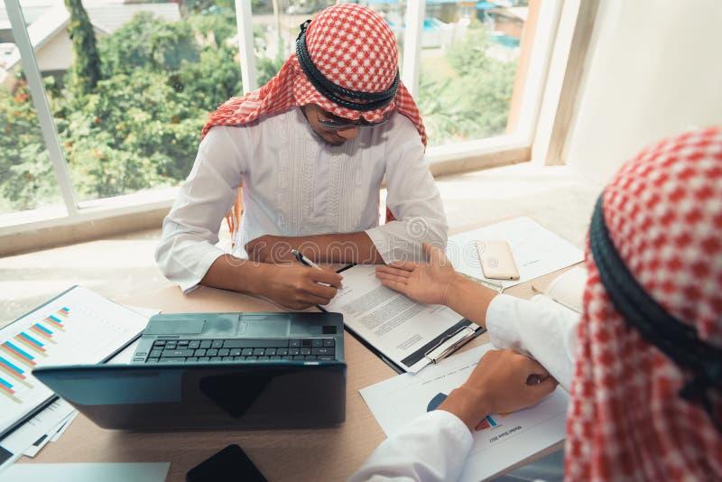De zakenlieden Arabier zijn samen binnen de overeenkomst van het handtekeningscontract royalty-vrije stock afbeeldingen