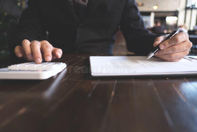 De zakenlieden berekenen het inkomen van de de uitvoerzaken op de houten lijst Bedrijfs concept stock afbeeldingen
