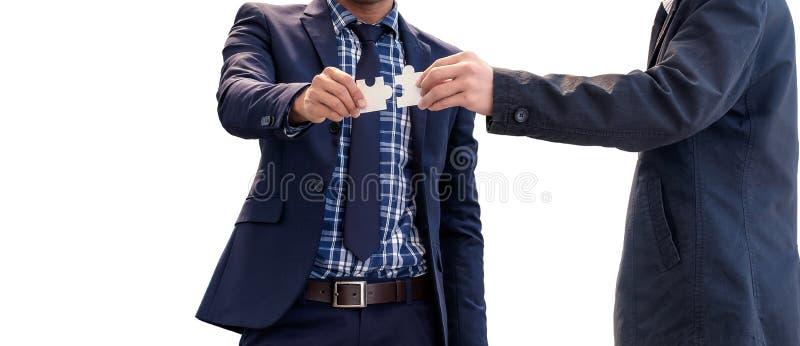 De zakenlieden houden puzzels voor elkaar op de witte rug stock afbeelding