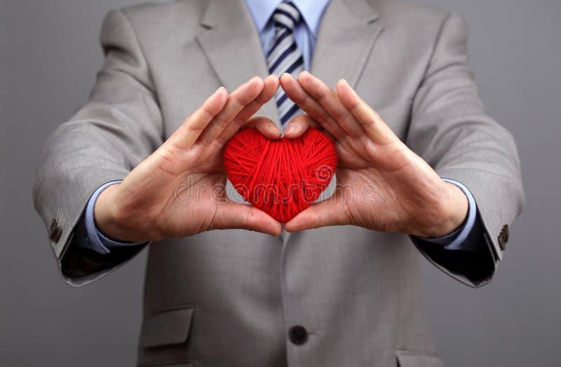 De zakenlieden houdt een rood hart stand stock afbeelding