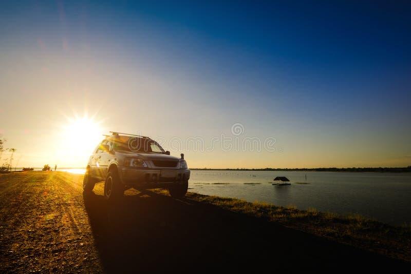 De zakenlieden met SUV-auto's parkeerden op de weg langs het reservoir Het letten van de op Zonsondergang royalty-vrije stock afbeeldingen