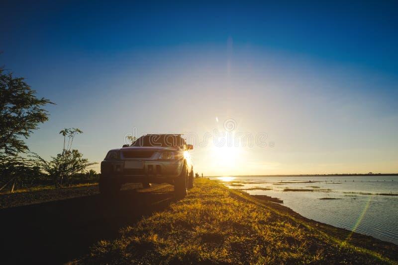 De zakenlieden met SUV-auto's parkeerden op de weg langs het reservoir Het letten van de op Zonsondergang royalty-vrije stock foto
