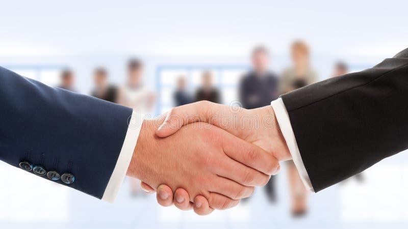 De zakenlieden overhandigen schok met bedrijfsmensen op achtergrond stock foto