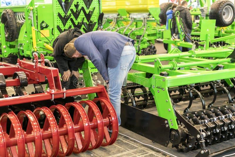 De zakenlieden overwegen landbouwmachines bij een tentoonstelling royalty-vrije stock afbeelding