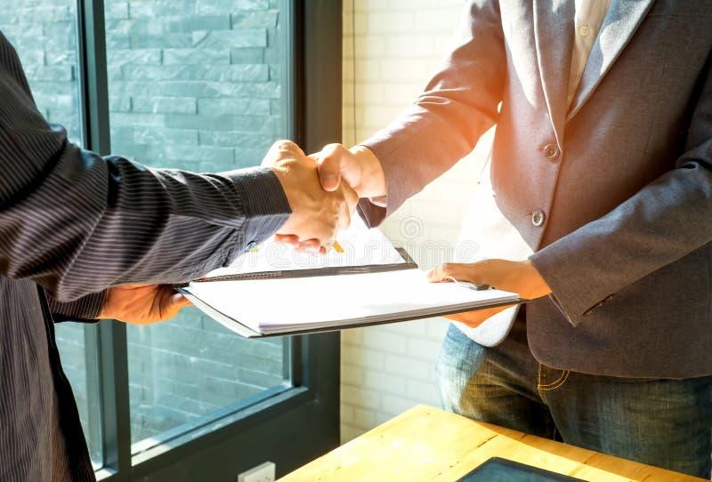 De zakenlieden schudden handen en ruilen bedrijfsdocumenten royalty-vrije stock afbeeldingen
