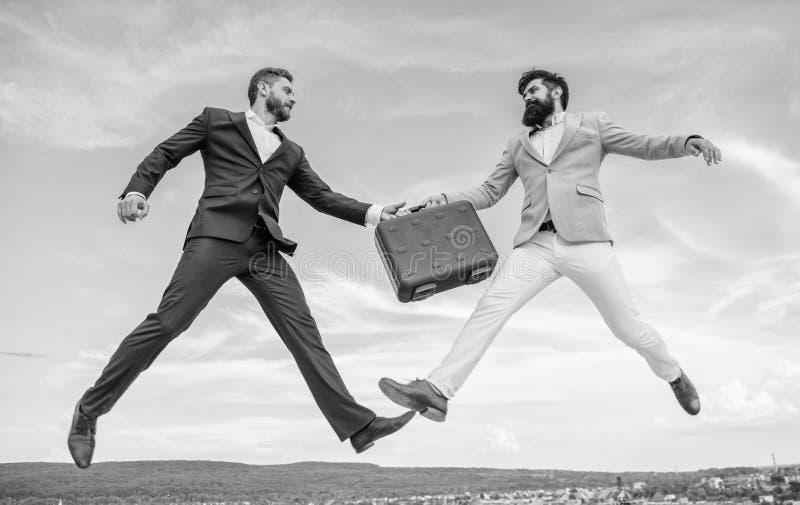 De zakenlieden springen vlieg medio lucht terwijl greepaktentas Geval met verhoging uw zaken Succesvolle transactie tussen royalty-vrije stock foto's