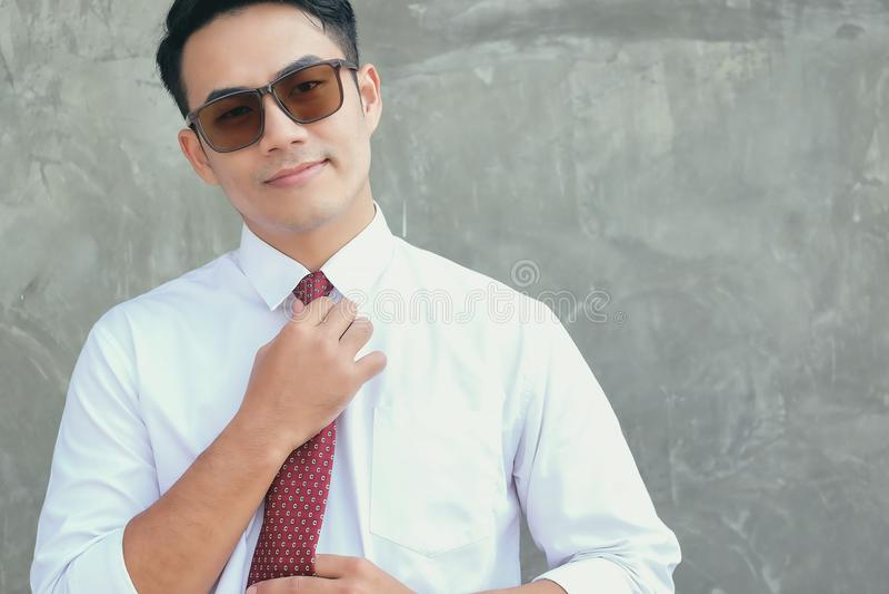 De zakenlieden verfraaien een rode stropdas op de dag van zijn eerste stock foto