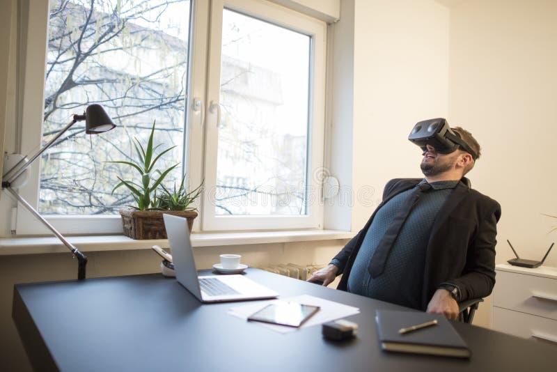 de zakenman beëindigt zijn werk en het overnemen van virtuele werkelijkheidsbeschermende brillen stock fotografie