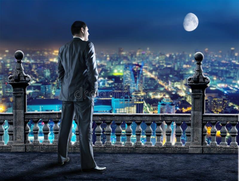 De zakenman bekijkt de avondstad royalty-vrije stock foto's