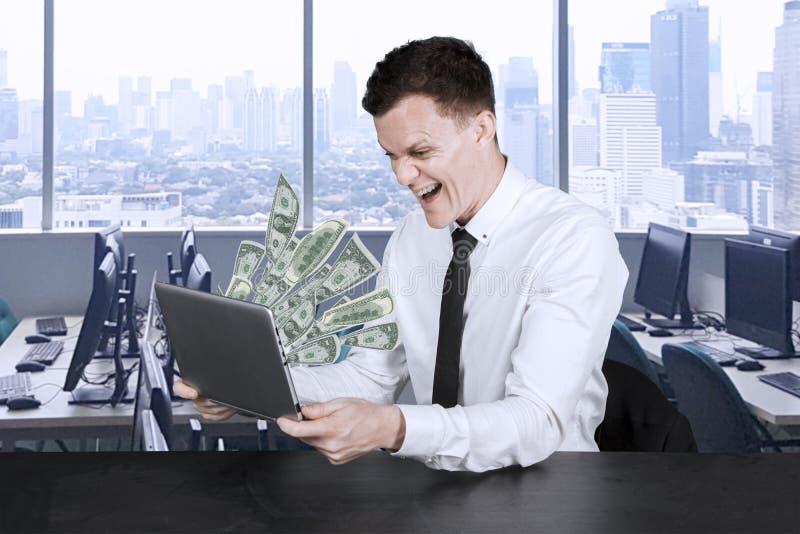 De zakenman bekijkt geld uit zijn laptop royalty-vrije stock foto