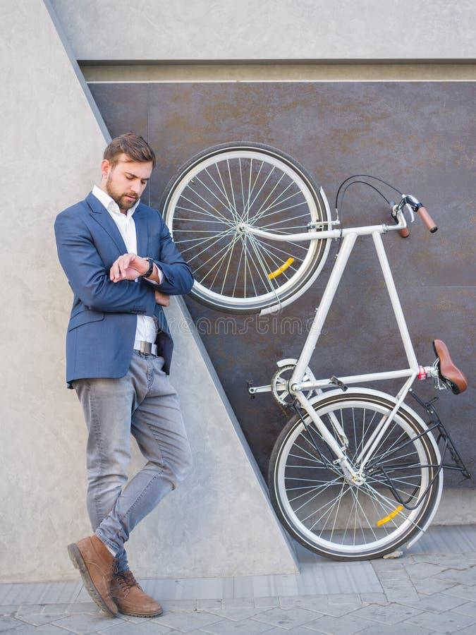 De zakenman bekijkt zijn horloge, naast een fiets wordt opgeheven op zijn achterste benen royalty-vrije stock foto's