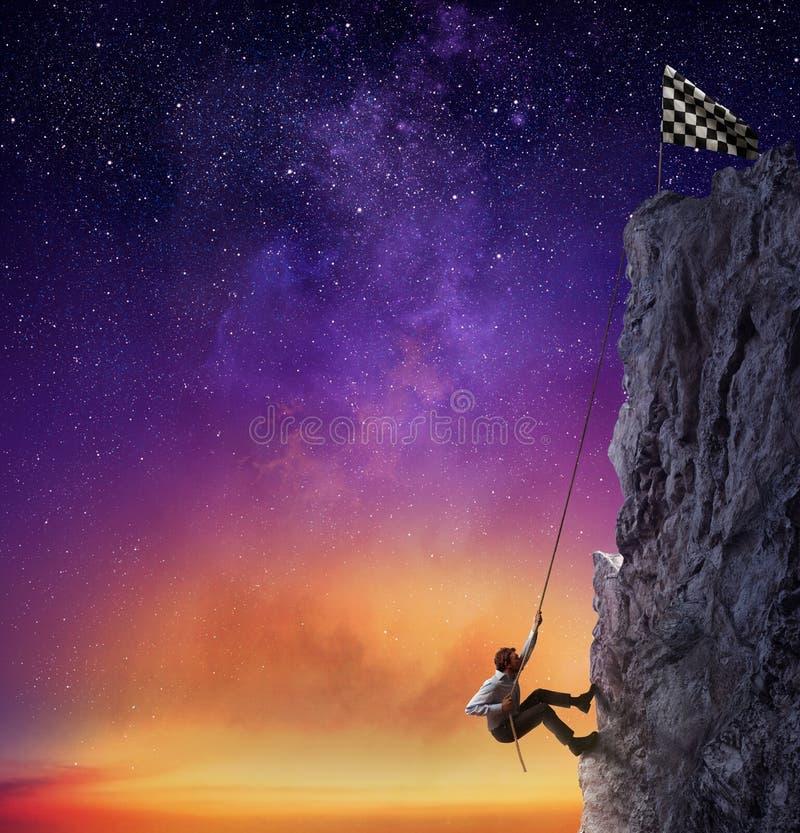 De zakenman beklimt een berg om de vlag te krijgen Voltooiings bedrijfsdoel en Moeilijk carrièreconcept stock fotografie