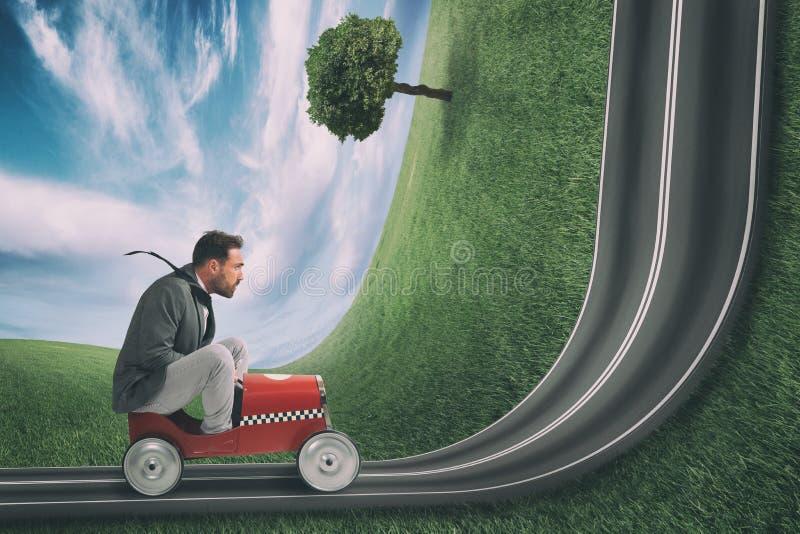 De zakenman beklimt een bergopwaartse weg met een kleine auto Moeilijk carrerconcept royalty-vrije stock afbeeldingen