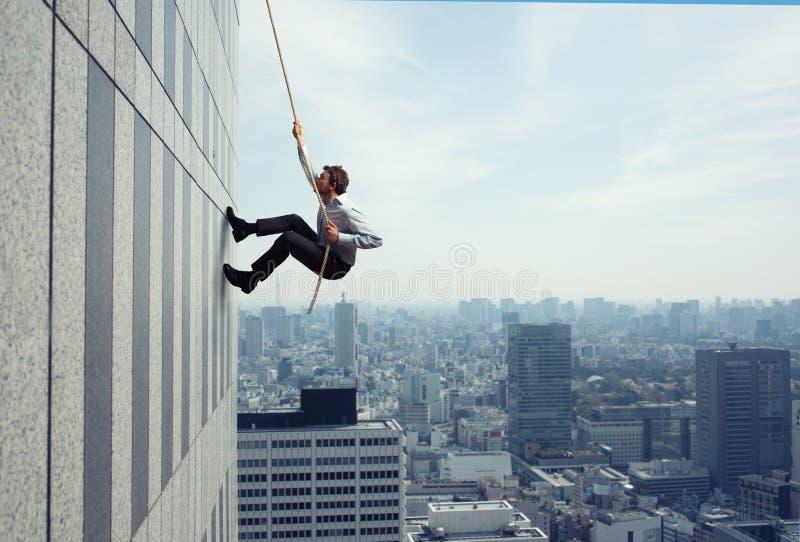 De zakenman beklimt een gebouw met een kabel Concept bepaling royalty-vrije stock afbeeldingen