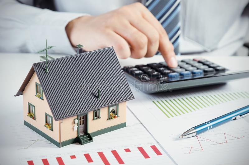 De zakenman berekent de kosten om huis te bouwen en te handhaven stock foto's