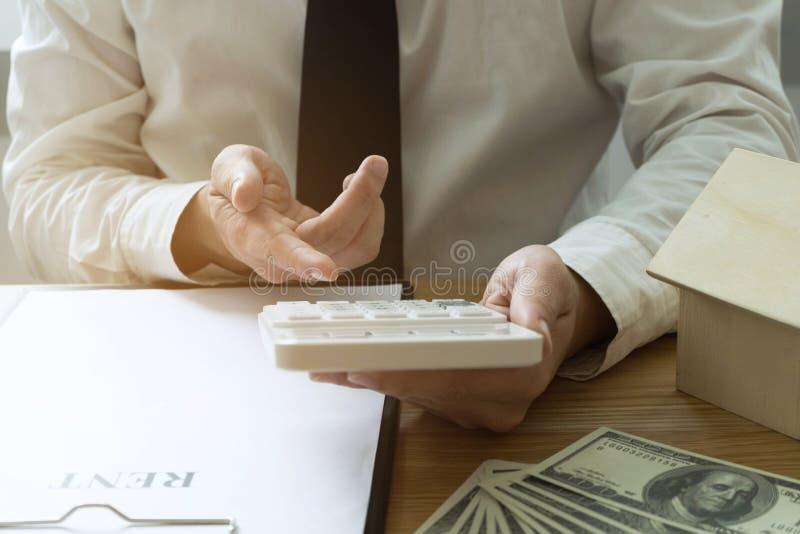 De zakenman berekent koopt - het huis van de verkoopprijs Het huis van de agentenverkoop stock foto's