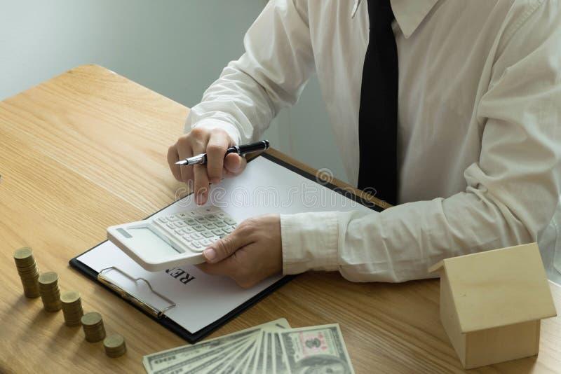 De zakenman berekent koopt - het huis van de verkoopprijs Het huis van de agentenverkoop stock afbeelding