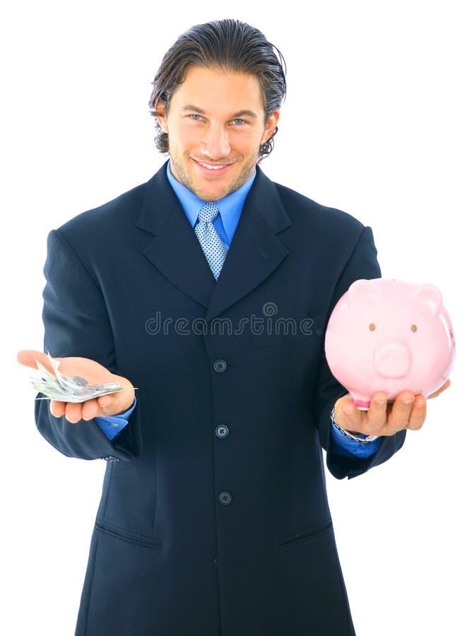 De zakenman bespaart Geld in Spaarvarken royalty-vrije stock afbeeldingen