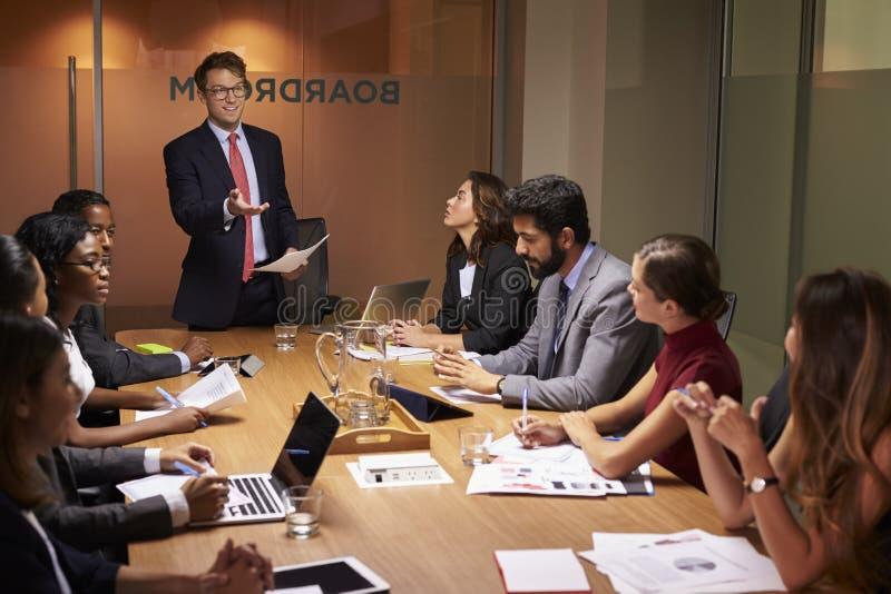 De zakenman bevindt zich gesturing aan collega's op een vergadering royalty-vrije stock afbeeldingen