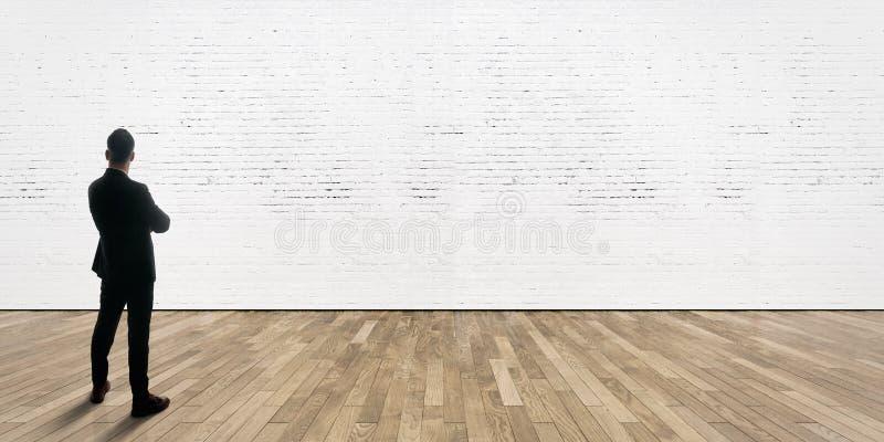 De zakenman bevindt zich tegenover bakstenen muur in galerijbinnenland met houten vloer stock fotografie