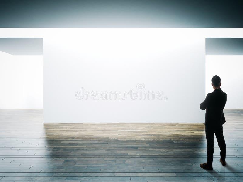 De zakenman bevindt zich tegenover grote witte muur in museumbinnenland met houten vloer horizontaal stock foto's