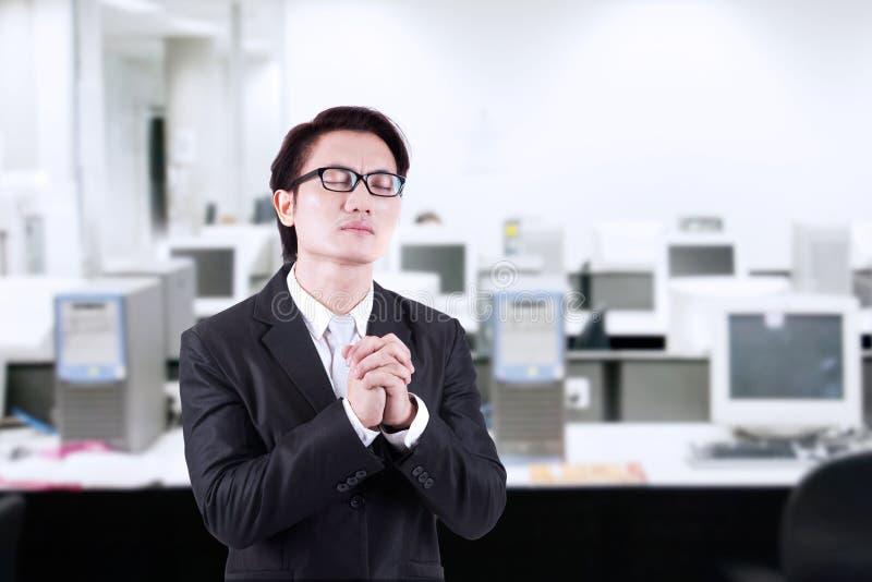 De zakenman bidt op kantoor stock fotografie