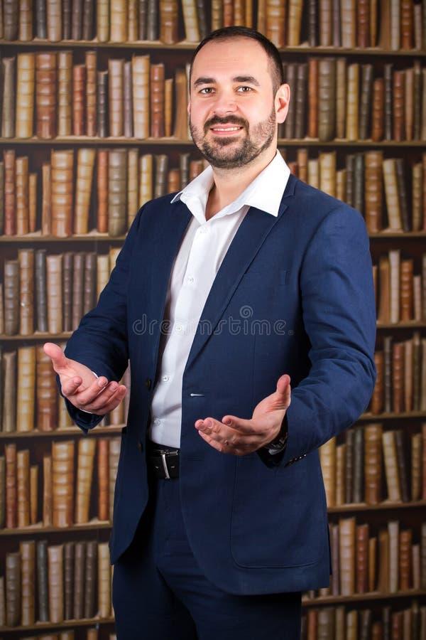 De zakenman in blauw kostuum heet in de bibliotheek welkom stock afbeeldingen
