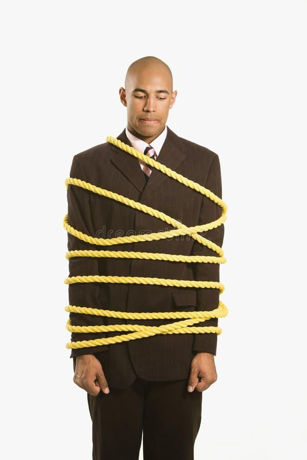 De zakenman bond kabel vast. stock fotografie