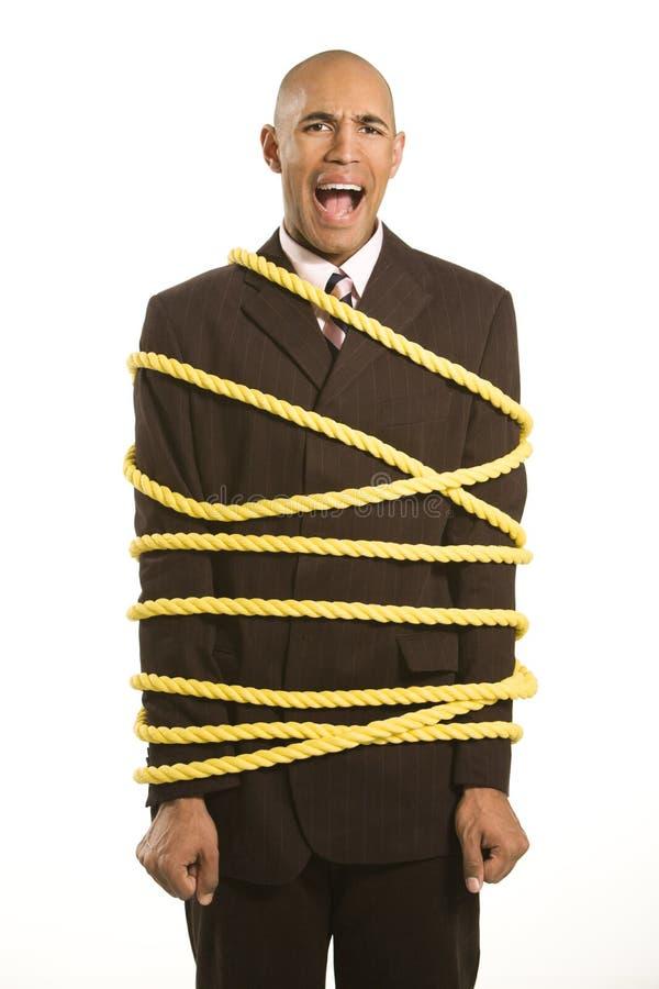 De zakenman bond kabel vast. stock afbeelding