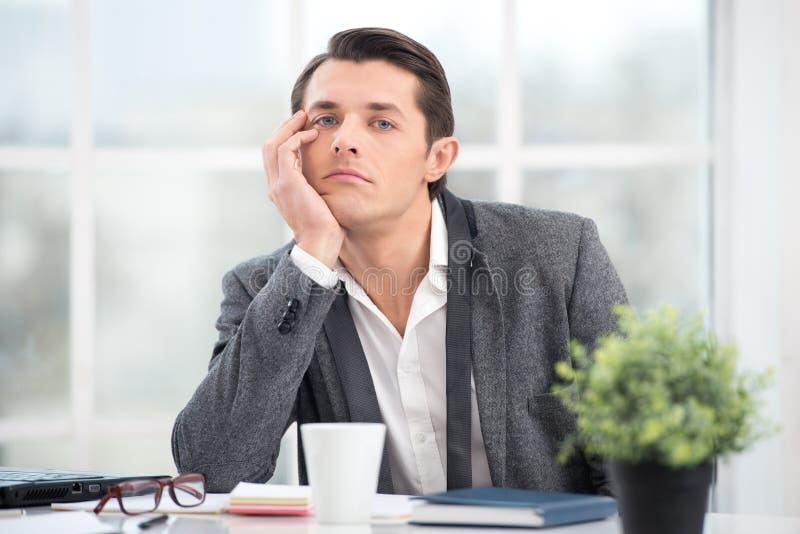 De zakenman is bored terwijl het werken in bureau stock afbeeldingen
