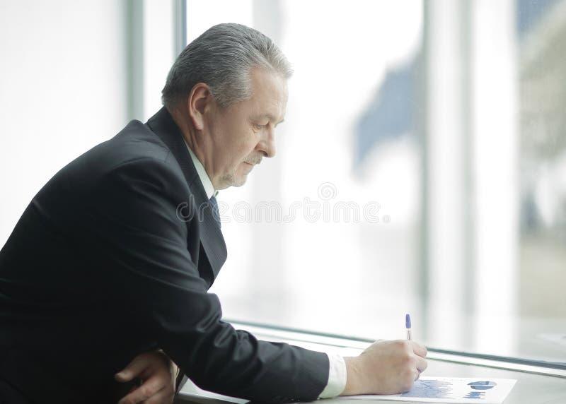 De zakenman controleert de financiële gegevens, die zich dichtbij het bureauvenster bevinden royalty-vrije stock foto's