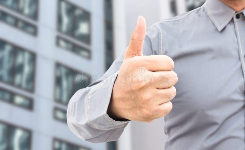De zakenman die duimen tonen ondertekent omhoog status in bureau royalty-vrije stock foto's