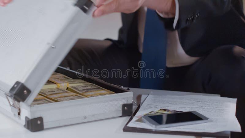De zakenman die geld in aktentas, terugslag voor politicus controleren, sluit omhoog royalty-vrije stock foto