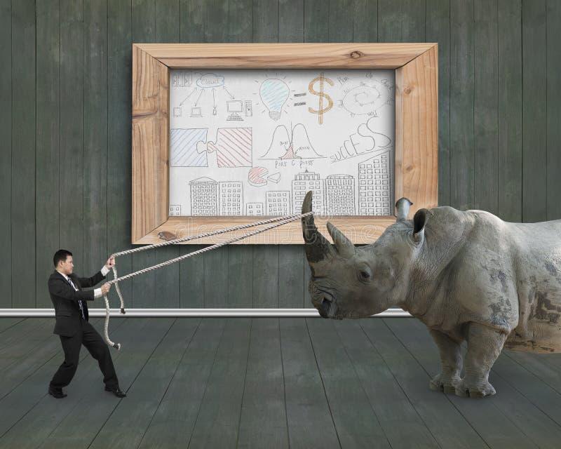 De zakenman die kabel trekken tegen rinoceroszaken concepten  stock afbeeldingen