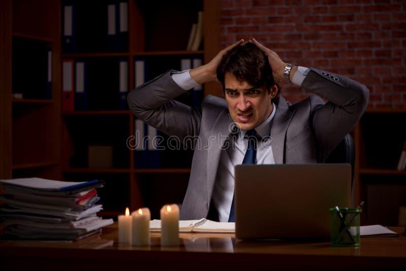 De zakenman die laat in bureau met kaarslicht werken stock foto