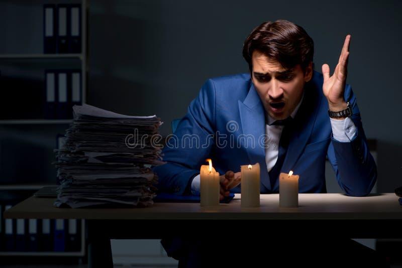 De zakenman die laat in bureau met kaarslicht werken royalty-vrije stock fotografie