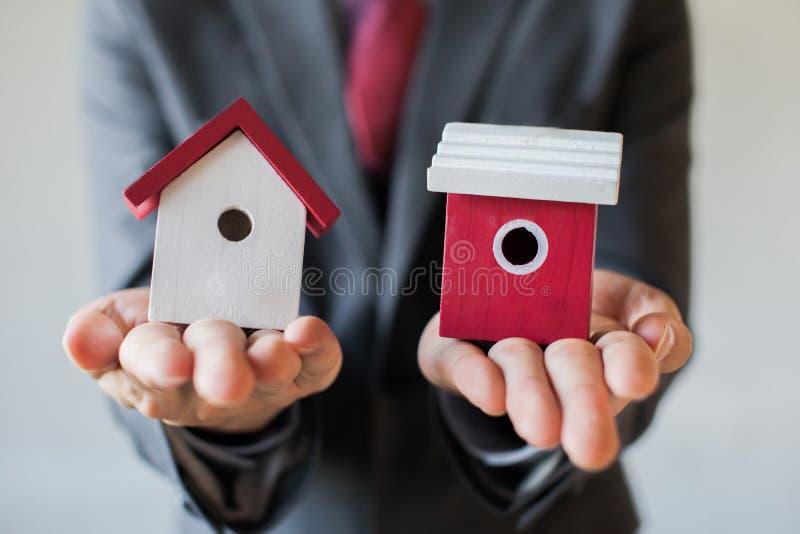 De zakenman die twee huizen houden en kan niet het kiezen van het juiste huis beslissen royalty-vrije stock afbeelding
