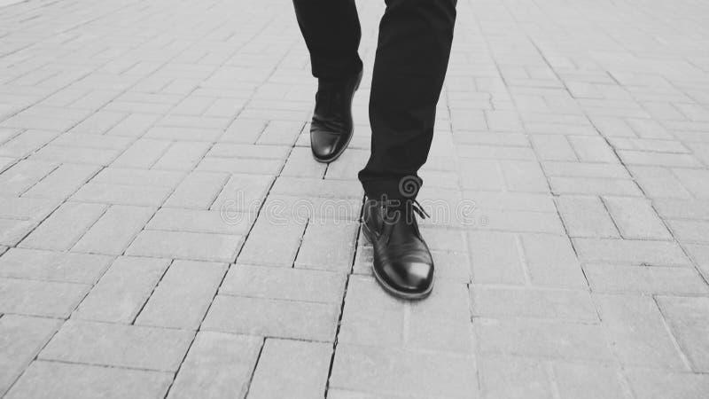 De zakenman die van de close-upmening in schoenen vooruit stoep lopen bij straat stock foto's