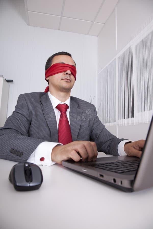 De zakenman die van de blinddoek met zijn laptop werkt stock fotografie