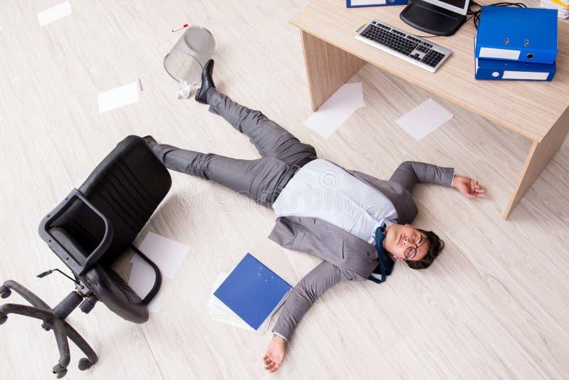 De zakenman dood op de bureauvloer stock afbeeldingen