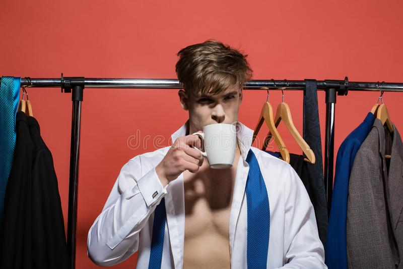 De zakenman drinkt thee of koffie in garderobe op rode achtergrond royalty-vrije stock foto