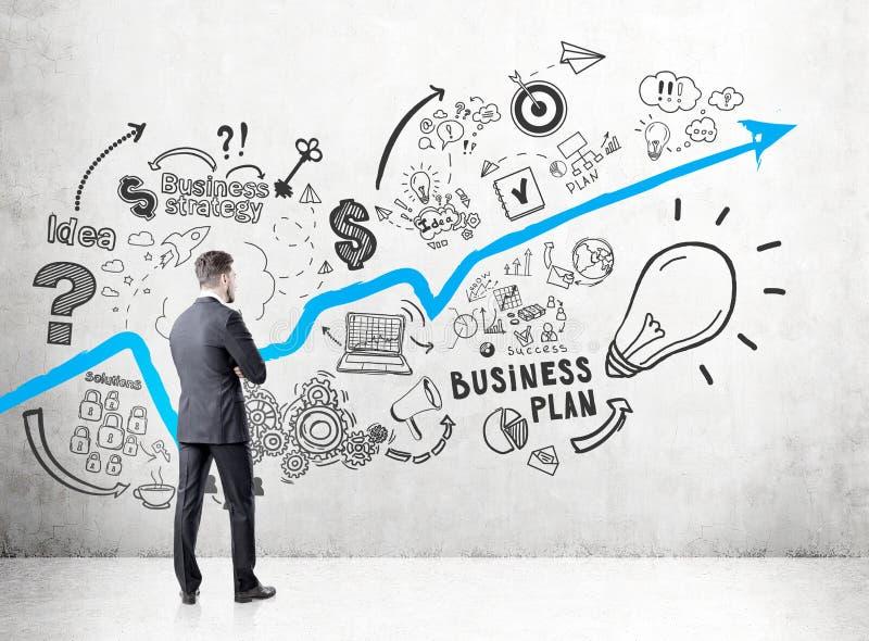 De zakenman in een donker kostuum die een concrete muur met een het groeien blauwe grafiek en businessplanpictogrammen bekijken s royalty-vrije stock afbeelding