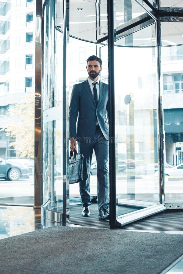 De zakenman in een fromal kostuum in een commercieel centrum gaat het gebouw met aktentas in royalty-vrije stock foto's